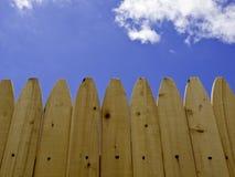 Sosnowego drewna ogrodzenie z niebieskim niebem i chmurami Zdjęcie Stock