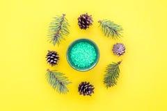 Sosnowi zdrojów kosmetyki, produkty dla skóry opieki Zielona aromatyczna zdrój sól blisko rozgałęzia się i konusuje na żółtym tło Zdjęcie Royalty Free