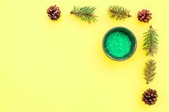 Sosnowi zdrojów kosmetyki, produkty dla skóry opieki Zielona aromatyczna zdrój sól blisko rozgałęzia się i konusuje na żółtym tło Obrazy Stock