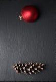 Sosny szyszkowa i Czerwona Bożenarodzeniowa piłka na czarnym tle Zdjęcia Stock