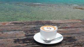 Sosowana kawa w białej filiżance na talerzu z łyżką na drewnianym wieśniaka stole, denny tło z morzem macha ruchu zdjęcie wideo