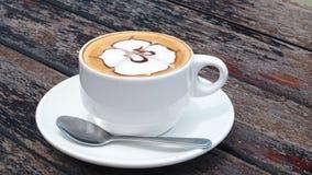 Sosowana kawa w białej filiżance na talerzu z łyżką na drewnianym wieśniaka stole, fala ruch Pić kawę z dennym widokiem zbiory
