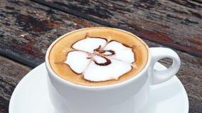 Sosowana kawa w białej filiżance na talerzu z łyżką na drewnianym wieśniaka stole, fala ruch Pić kawę z dennym widokiem zbiory wideo