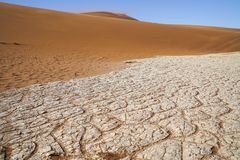 Sossusvlei dunes at Dead Vlei. Oorange dunes and white salt pan cracked into patterns royalty free stock image