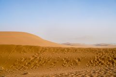 Sossusvlei dunes at Dead Vlei. Wind blown patterns in orange dunes fade into dusty hills in background stock image
