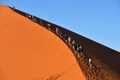 SOSSUSVLEI, NAMIBIA, DUNE 45. SOSSUSVLEI, NAMIBIA - JAN 29, 2016: Tourists climb Dune No.45 most popular dune in the whole World, Namibia, Africa royalty free stock photos