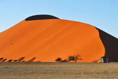 SOSSUSVLEI, NAMIBIA, DUNE 45. SOSSUSVLEI, NAMIBIA - JAN 29, 2016: Tourists climb Dune No.45 at sunrise, most popular dune in the whole World, Namibia, Africa royalty free stock images