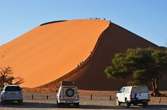 Sossusvlei, Namibia, Africa. Sossusvlei, Namibia - Jan 29, 2016: Tourists climb Dune No.45 at sunrise, most popular dune in the whole World, Namibia, Africa stock images