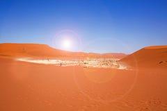 Sossusvlei-Wanne in Namib Naukluft mit orange Dünen und einem hellen blauen Himmel Stockbilder