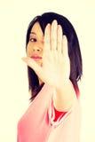 Sosténgase encendido, gesto de la parada mostrado por la mujer joven Imágenes de archivo libres de regalías