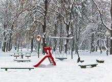 Sosta della strumentazione del campo da giuoco dei bambini nell'inverno Immagini Stock
