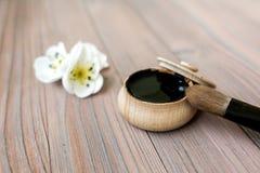 Sostanza nera in barattolo di legno su un fondo di legno Fotografia Stock