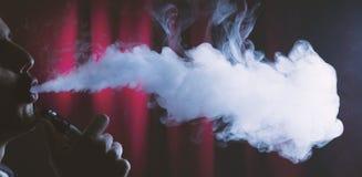 Sostener el cigarrillo electrónico o el cig de e y vaping las nubes Fotografía de archivo