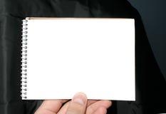 Sostener el cuaderno espiral en blanco en fondo abstracto Fotografía de archivo libre de regalías