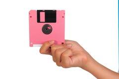 Sostener el disco blando en el fondo blanco Ordenador del disco blando adentro Foto de archivo