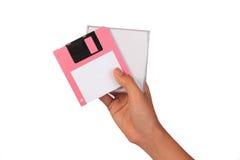 Sostener el disco blando en el fondo blanco Ordenador del disco blando adentro Imagen de archivo libre de regalías