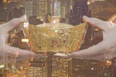 Sostener el lingote chino del oro del Año Nuevo, opinión de la ciudad de la noche Fotografía de archivo