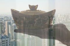 Sostener el lingote chino del oro del Año Nuevo, opinión de la ciudad del día Fotografía de archivo