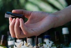 Sostener la botella de aceite esencial Foto de archivo libre de regalías