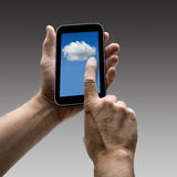 Sostener la pantalla de las nubes en el teléfono elegante foto de archivo