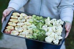 Sostener un disco de verduras crudas para cocer Imagen de archivo