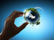 Sostener un globo de la tierra que brilla intensamente en su mano Foto de archivo libre de regalías