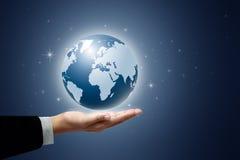 Sostener un globo de la tierra que brilla intensamente en sus manos Fotografía de archivo libre de regalías