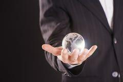 Sostener un globo de la tierra que brilla intensamente en sus manos Imagen de archivo
