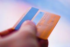 Sostener una tarjeta de crédito anaranjada, pagando algo Fotos de archivo libres de regalías