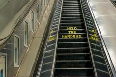 Sostenga el aviso de la barandilla en una escalera móvil Fotografía de archivo libre de regalías