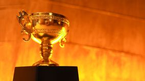 Sostenga il trofeo dorato disposto sullo spazio di legno della copia del fondo dell'oro fotografie stock