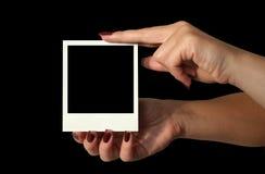 Sosteniendo la polaroid en blanco - fondo negro profundo #2 Imagen de archivo libre de regalías