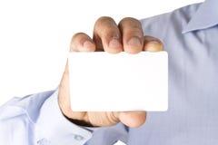Sosteniendo la tarjeta blanca del banco similar a la tarjeta de la tarjeta de cajero automático o de crédito o al de Imagenes de archivo