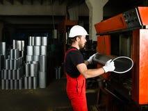 Sosteniendo un tubo manufacturado de plata del metal, imagenes de archivo