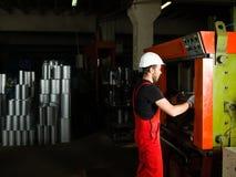 Sosteniendo un tubo manufacturado de plata del metal, foto de archivo