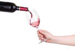 Sosteniendo una taza de vino rojo vierta aislado en blanco Imágenes de archivo libres de regalías