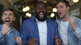 Sostenitori maschii emozionanti che si rallegrano vittoria del gruppo, risultato di campionato, scopo video d archivio