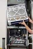 Sostituendo un filtro per una fornace con la copertura fuori immagine stock