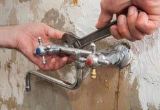 Sostituisca un rubinetto di acqua della cucina, idraulico delle mani con regolabile Fotografia Stock Libera da Diritti