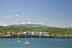 Sosua Bay,Sosua, Dominican Republic. A view of the west shore of the Bay at Sosua, Dominican, showing a modern resort, hills in the background and two catamarans Royalty Free Stock Images