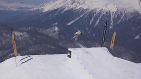 SOTCHI, RUSLAND - APRIL 2, 2016: De skiërsprong van springplank, maakt volledige tik in lucht Landschap van bergen Sport stock videobeelden