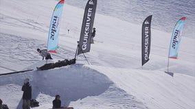 SOTCHI, RUSLAND - APRIL 2, 2016: De Snowboardersprong van springplank, maakt volledige tik bij de skitoevlucht SNEEUW BERGEN stock video