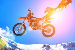 05 04 2018 Sotchi, Russie, coureur sur une moto en vol, saute et décolle sur un tremplin contre le neigeux Photo stock