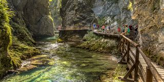 Soteska vintgar gorge boardwalk with tourists. Soteska vintgar gorge with tourists walking on boardwalk along river on sunny day Stock Images