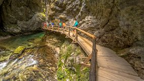 Soteska vintgar gorge boardwalk along river. Soteska vintgar gorge with tourists walking on boardwalk along river on sunny day Royalty Free Stock Image