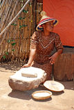 Sotho woman cooking maize meal. LESEDI CULTURAL VILLAGE,SOUTH AFRICA - JAN 1:Sotho woman in handmade dress  and conical hat cooking maize meal at tribal house on Royalty Free Stock Photos