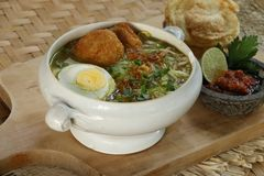 Soto Ayam. Indonesian chicken clear soup, served with chili paste, lime, and crisp crackers Royalty Free Stock Photography