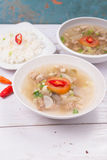 Soto or coto or indonesian beef soup served with white rice, tomato, soy, and green onion. On wood base Royalty Free Stock Photo