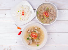 Soto or coto or indonesian beef soup served with white rice, tomato, soy, and green onion. On wood base Royalty Free Stock Image