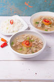 Soto or coto or indonesian beef soup served with white rice, tomato, soy, and green onion. On wood base Royalty Free Stock Photos